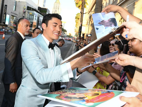 Henry Golding signs autographs for fans at the premiere