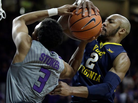 West Virginia guard Jevon Carter (2) blocks a shot by Kansas State guard Kamau Stokes (3) during the second half of an NCAA college basketball game in Manhattan, Kan., Monday, Jan. 1, 2018. West Virginia defeated Kansas State 77-69. (AP Photo/Orlin Wagner)
