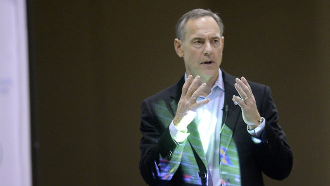 A projector flashes a football play as Michigan State coach Mark Dantonio speaks to high school football coaches in Lansing on Jan. 16, 2015.