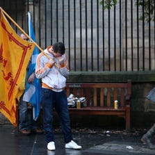 """Dejected """"Yes"""" vote campaigners make their way home along the Royal Mile after the people of Scotland voted no to independence on Thursday."""