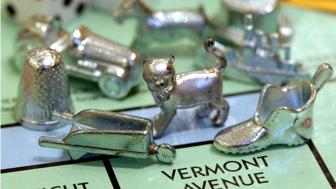 In this Feb. 5, 2013 file photo, the thimble game piece, left, sits among other Monopoly tokens at Hasbro Inc., headquarters in Pawtucket, R.I. The thimble will no longer be a game piece in Monopoly, rejected in 2017 in a campaign to determine the tokens for the next generation of the game.