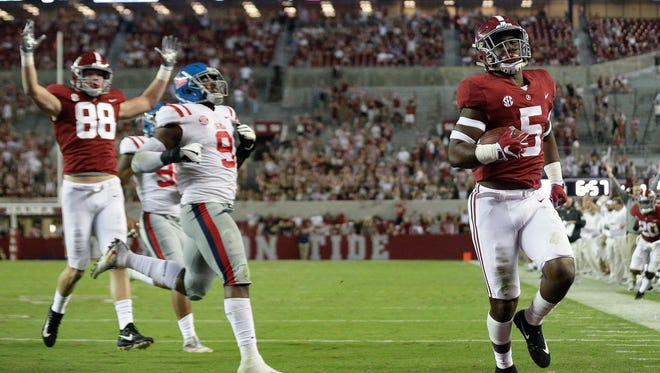 Alabama tight end Ronnie Clark scores a touchdown against Ole Miss and defensive tackle Breeland Speaks (9).