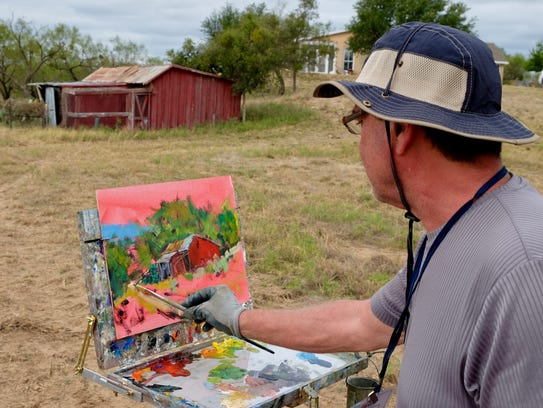 Bob Beck of Manitowoc, Wisc. paints a ranch scene during