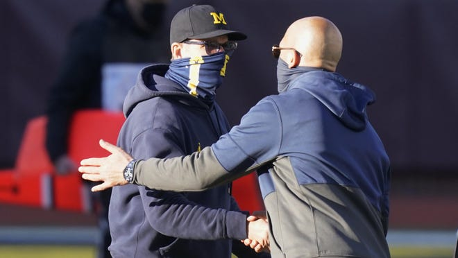 Michigan head coach Jim Harbaugh, left, greets Penn State head coach James Franklin after an NCAA college football game, Saturday, Nov. 28, 2020, in Ann Arbor, Mich. Penn State won 27-17.