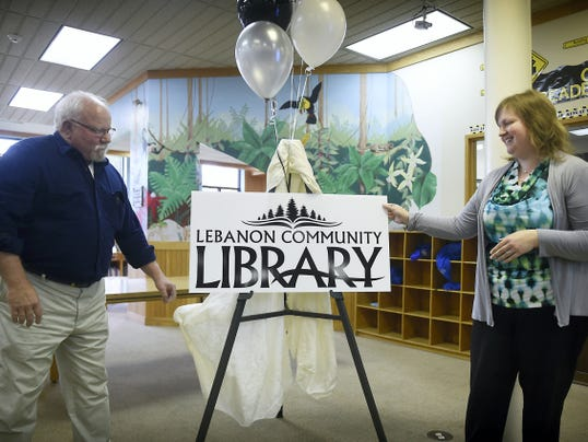 Lebanon Community Library Board of Directors President Bill Smeltzer and library director Michelle Hawk reveal the library's new logo, designed at no cost by KB Graphix. The library celebrated the 30th anniversary of its current location at Seventh and Willow streets on Wednesday.