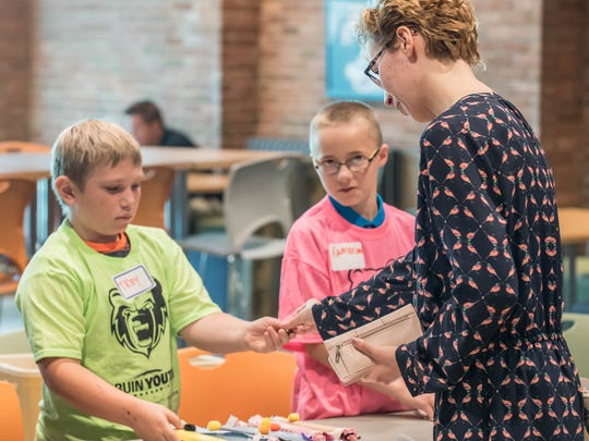 Trey Willavize, left, and Kameron Cooper make a sale at a young entrepreneurs event at Kellogg Community College on Wednesday.