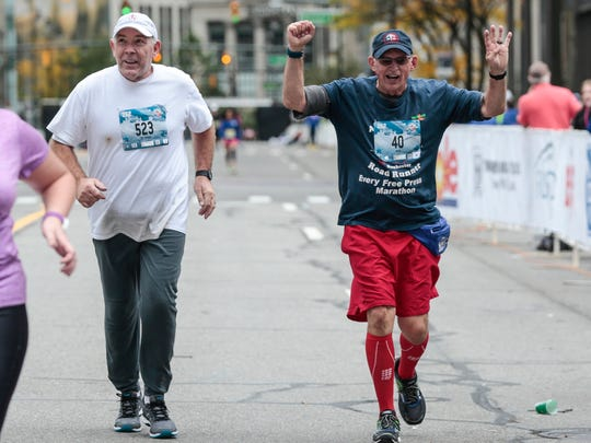 Garry Watson of Rochester Hills, right, celebrates as he runs acorss the finish line during the 40th Annual Detroit Free Press/Chemical Bank Marathon in Detroit on Sunday, Oct. 15, 2017. Next to Watson is Thomas Wieske of Westland.
