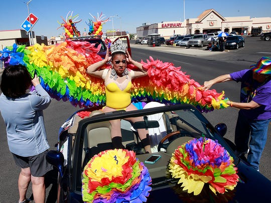 Lady Shug, center, dons her attire before the Pride parade on Saturday  in downtown Farmington.