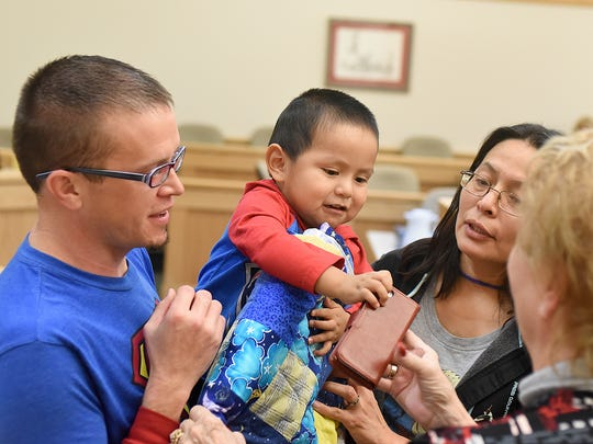 Teddy Jeffrey, 2, is given a quilt by members of Bethany Christian Church on Friday at the Eleventh Judicial District Court in Farmington, surrounded by his father, Randall Jeffrey, left, and his mother, Rolanda Jeffrey.