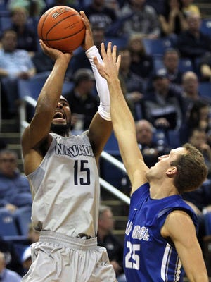 Wolf Pack guard D.J. Fenner scores a 3-point basket in front of Air Force Falcons forward Kyle Broekhuis last season. The teams face off Wednesday.