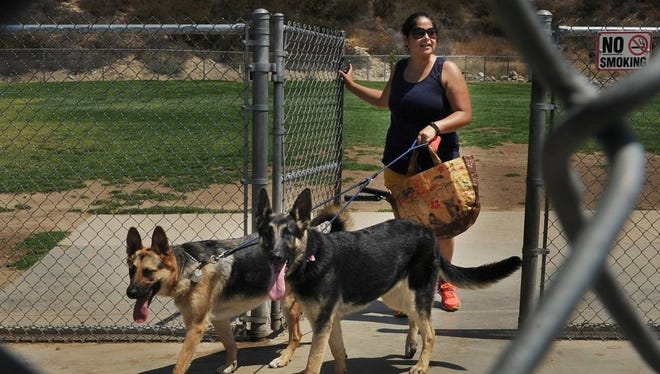 A dog park like this one in Simi Valley, complete with fencing, has been approved for Fillmore. It will be built at Two Rivers Park. Here, Regina Samayoa leaves the Simi dog park with her German shepherds Moose, left, and Mia.