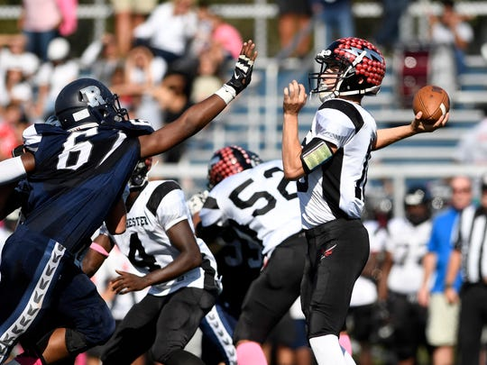 Manchester quarterback Antonio Bisciotti, right, throws the ball with pressure from Rutherford. Rutherford defeated Manchester 28-0 on Saturday, October 21, 2017 in Rutherford, NJ.
