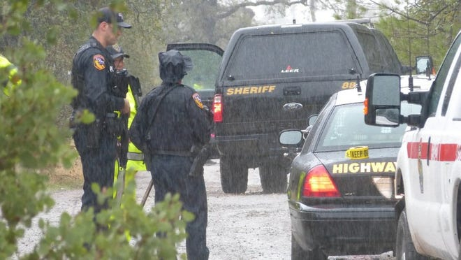 Jim Schultz/Record Searchlight Law enforcement officials wait in a steady rain during a standoff Thursday on Yuki Yama Lane east of Redding.