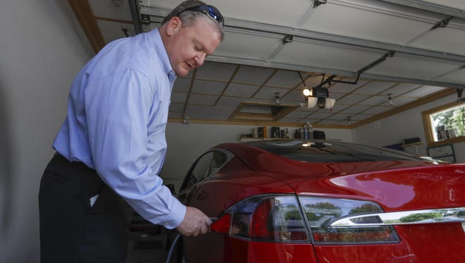 In this Thursday, July 13, 2017, photo, Jeff Solie plugs in his electric Tesla sedan at his home, in New Berlin, Wis. Electric cars are seeing growing support around the world. But there's a problem: There aren't enough places to plug those cars in. The nearest fast-charging Tesla Superchargers are 45 miles away. There are some public charging stations in nearby Milwaukee, at hotels and shopping centers, but Solie relies almost entirely on the charging system he set up in his garage.
