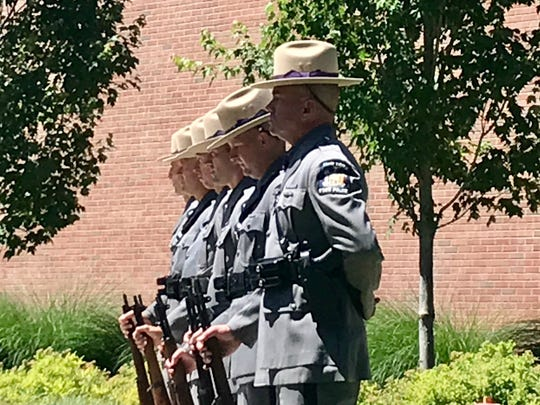 Officers prepare for 21-gun salute at Trooper Nicholas Clark's funeral service Sunday.