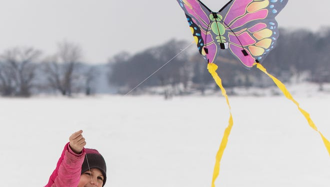 """Addy Nysse, 10, of Pewaukee flies a kite on Pewaukee Lake during the """"Fly a Kite on Ice"""" event hosted by Silly Willyz toy store in 2015."""