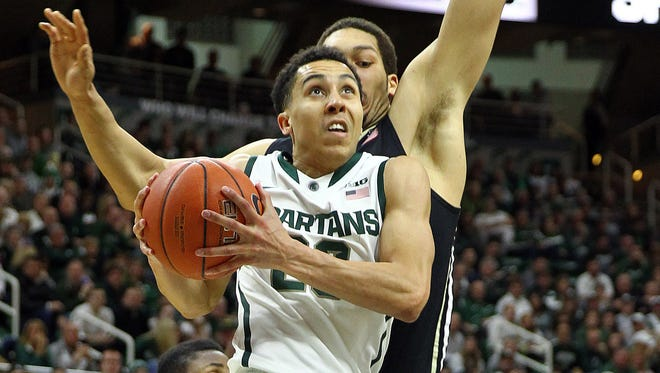 Michigan State Spartans guard Travis Trice (20) drives to the basket against Purdue Boilermakers center A.J. Hammons (20) during the 2nd half of a game at Jack Breslin Student Events Center.