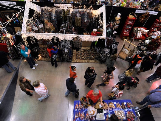 Shoppers walk between booths during Christmas in November