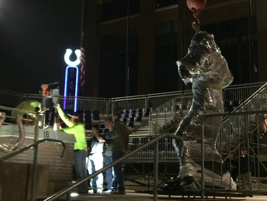 A red crane supports Peyton Manning as crews work to