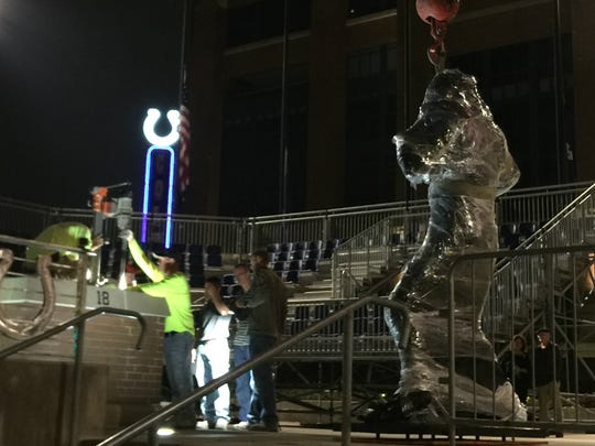 A red crane supports Peyton Manning as crews work to prepare the base of the bronze statue.
