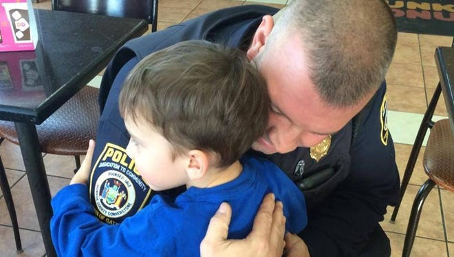 """Gates police officer Shawn O'Mara and young boy embrace in an impromptu hug in 2014. Gates police will host a """"Hug a Cop"""" party at the Walmart Supercenter, 2150 Chili Road on July 16, 2016."""