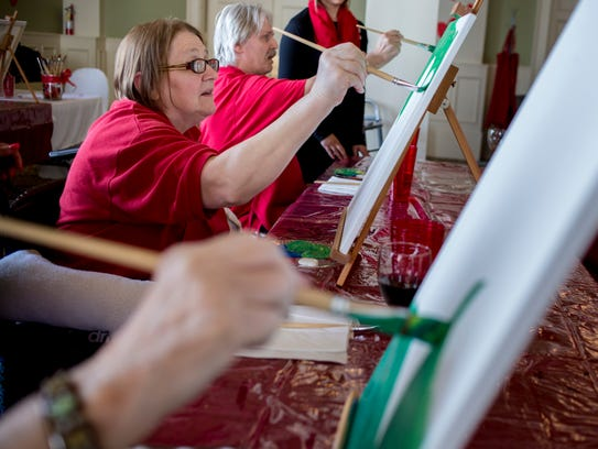 Resident Mary White paints with others during a therapeutic