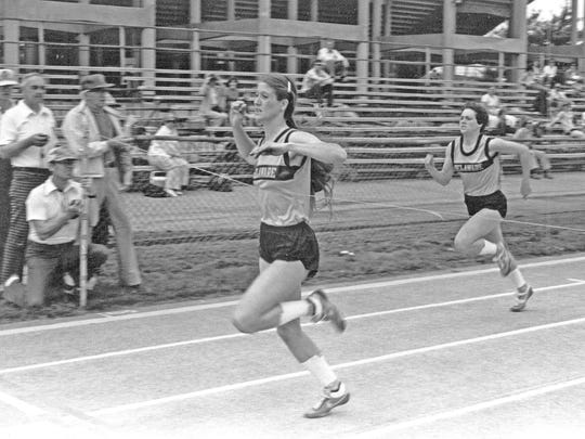Pam Hohler crosses the finish line to win a race at the University of Delaware.