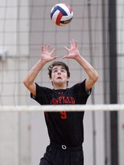 Penfield's Jett Klintworth reaches to pass a ball over his head.