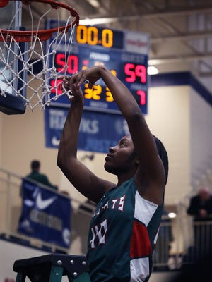 FILE – Lawrence North's Lamina Cooper cuts down part of the net after the Wildcats' win over Pike in the girls Class 4A Regional at Decatur Central, Feb. 21, 2015.