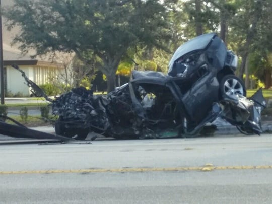 A burned car that crashed Sunday, March 5, 2017, in Fort Pierce is loaded on a tow truck.
