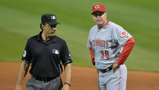 Cincinnati Reds manager Bryan Price (38) talks with first base umpire Phil Cuzzi (L) before requesting a video replay review in the ninth inning against the Cleveland Indians at Progressive Field.