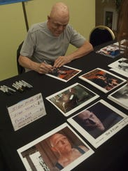Michael Berryman, pictured signing autographs at the