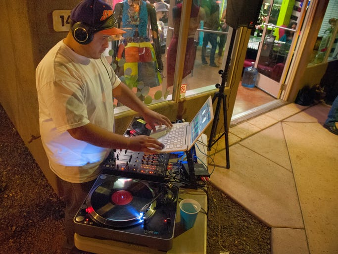 M. Rocka works the decks in front of Nostra Style House on Roosevelt Row in Phoenix during the First Friday Artwalk on Friday, April 4, 2014.