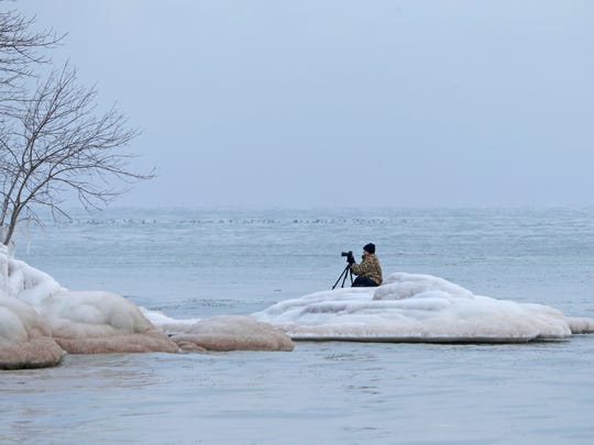 """""""I'm trying to get the photo nobody else has,"""" Tim Holte of Milwaukee said as he perched himself Wednesday on a mound of ice near Bradford Beach in Milwaukee while taking photos of the Lake Michigan shoreline that's covered in ice."""