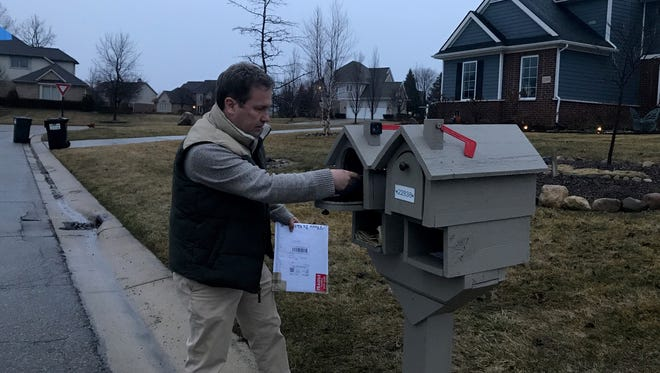 South Lyon resident Keith Ledbetter removes mail from his mailbox on Thursday. The Tanglewood subdivision Ledbetter resides in has been plagued recently by a variety of mail issues.
