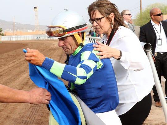 Jockey Tracy J. Hebert dismounts from Runaway Ghost