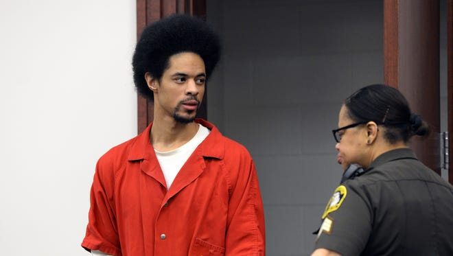 Marquay McCoy, 20, right, looks toward his family in court Friday in Lansing.