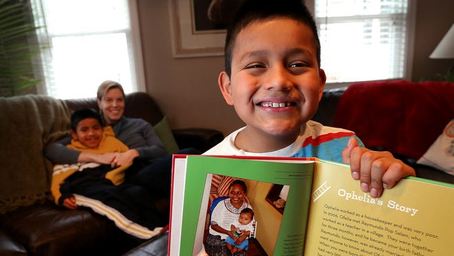 Noah Geppert holds a book with a photo of his birth mother Ofelia. Noah recently sold his tickets to a Indiana Pacers game, now $400 is on its way to his birth mother in Guatemala. His adopted mother Caren and brother Alex snuggle on the couch in the background.