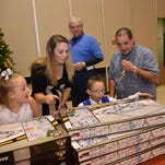 Rotarian Elizabeth Randall (left) helps Penelope Jackson look for toys for her two sons and daughter at the Doll & Toy Fund Distribution held Saturday at Alexandria Convention Hall. The Doll & Toy Fund is sponsored by The Town Talk and the Rotary Club of Alexandria.