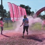 A runner runs through pink-colored corn starch during The Color Run Tropicolor World Tour 2016 at the Central Florida Fairgrounds on Jan. 16.