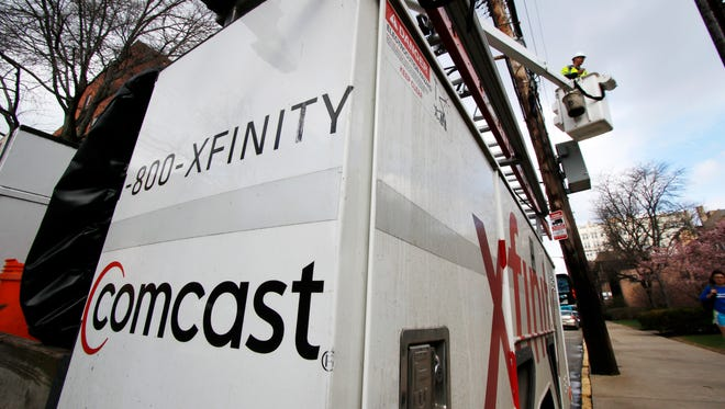 File photo taken in March 2017 shows a Comcast employee at work in Pittsburgh, Pa.