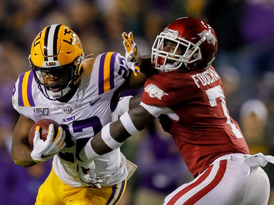Nov 23, 2019; Baton Rouge, LA, USA; LSU Tigers running back Clyde Edwards-Helaire (22) carries the ball as Arkansas Razorbacks defensive back Joe Foucha (7) defends during the first half at Tiger Stadium. Mandatory Credit: Stephen Lew-USA TODAY Sports