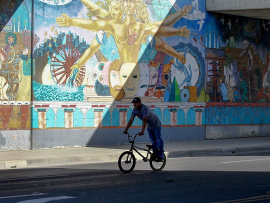 A man rides on the pegs of his bike under a overpass