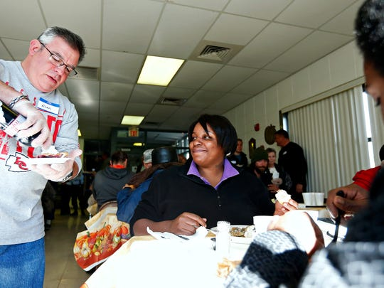 A Salvation Army volunteer serves pie to Lisa Jones and Glenn Phillips during the Salvation Army's annual Community Thanksgiving Lunch served at the Salvation Army Harbor House in Springfield, Mo. on Nov. 24, 2016.