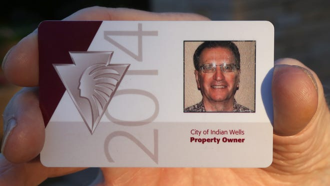 Indian Wells resident Andy Elchuck holds his IW resident card in front of the city hall building Wednesday, October 15 2014.