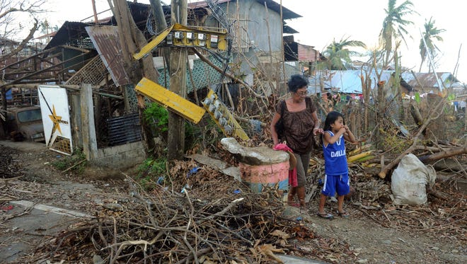 A woman and a girl inspect an area devastated by Super Typhoon Haiyan in Estancia in the province of Iloilo on Monday.