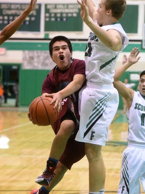 Shiprock's Kevin Begay drives to the basket against Farmington's Sol Rascon on Jan. 26 at Scorpion Gym in Farmington.
