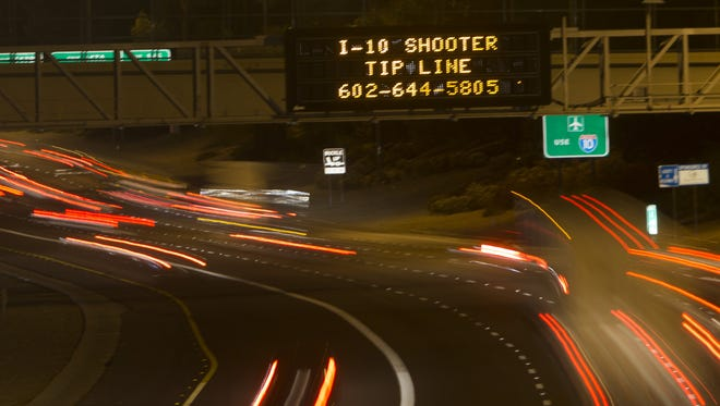 A sign giving the number of the shooter tip line shines above vehicles on  Interstate 10 at Seventh Street in Phoenix on Sept. 10, 2015.