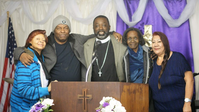 Rev. Reginald D. Price, center, surrounded by some of his congregation at Antioch Missionary Baptist Church.