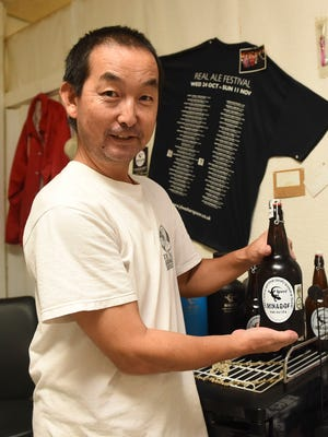 Ishii Brewing Co. President and Brewmaster Toshi Ishii with one of his 32-ounce Minagof beers in Tamuning on July 17, 2018.